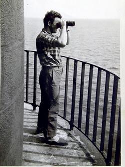 Paul Courraud scrute l'horizon en haut d'un phare.